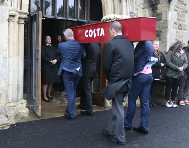 The funeral of Karen Lloyd who was buried in a Costa coffee coffin because of he love of latte's. See SWNS story SWCOFFEE; A latte lover who lost her battle with cancer was laid to rest in a COSTA COFFEE-inspired coffin. Brave Karen Lloyd was known amongst her friends and family for her love of shopping and caffeine. So when the mother-of-two recently passed away, it was decided she would be given a fitting send off. Karen, 51, had a specially made Costa Coffee-liveried coffin made, with the words 'one shot, extra hot skinny latte', written underneath.